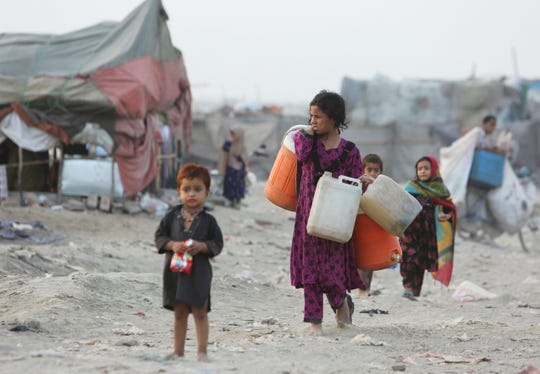 Afghan refugees who fled their homeland due to war and famine, are on their way to collect clean water in slums of Lahore, Pakistan, Wednesday, June 19, 2019. Pakistan will also observe the World Refugee Day tomorrow with other countries, launched by the UN Refugee Agency, and held every year on June 20th, aims to honors the courage of people who are forced to flee their homeland.