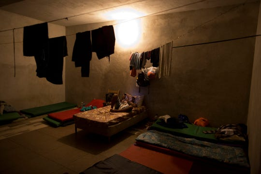 A Cuban man looks at his phone as he prepares for bed in a dormitory shared by Cuban migrants, at the Good Shepherd shelter in Tapachula, Mexico.
