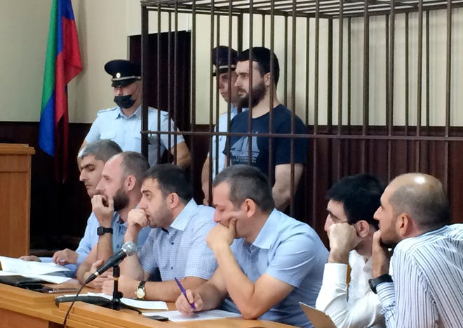 In this photo taken on Sunday, June 16, 2019, Abdulmumin Gadzhiev, the religious affairs editor of the independent weekly Chernovik, stands in a cage in a court room in Makhachkala, the Caspian Sea province of Dagestan, Russia, Sunday, June 16, 2019.