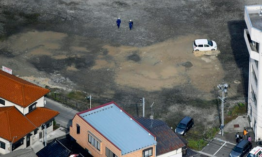 City officials inspect an area hit by liquefaction in Tsuruoka, Yamagata prefecture, northwestern Japan, Wednesday, June 19, 2019, after an earthquake.
