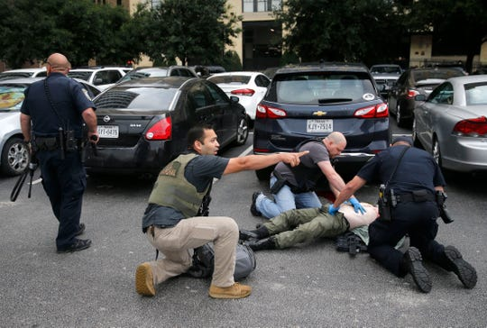 Members of the Department of Homeland Security and the U.S. Marshal's Service tend to the downed shooter after shots were fired Monday morning, June 17, 2019 at the Earle Cabell federal courthouse in Dallas.