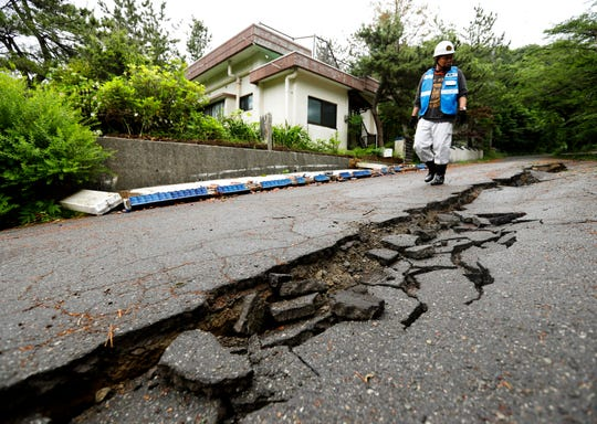 A city official inspects the damage of a road in Tsuruoka, Yamagata prefecture, northwestern Japan, Wednesday, June 19, 2019, after an earthquake.