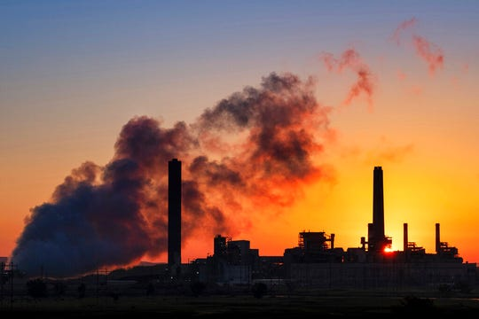 In this July 27, 2018, file photo, the Dave Johnson coal-fired power plant is silhouetted against the morning sun in Glenrock, Wyo. The Trump administration announced on Wednesday, June 19, 2019, that it has rolled back a landmark Obama-era effort targeting coal-fired power plants and their climate-damaging pollution.