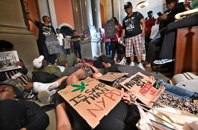 Protesters urging legislators to pass Marijuana legislation lay on the floor outside the Assembly Chamber doors at the state Capitol Wednesday, June 19, 2019, in Albany, N.Y.