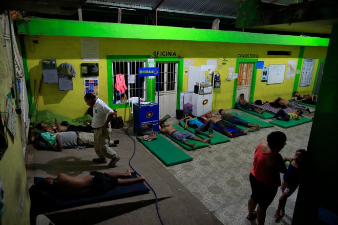 Male migrants bed down for the night on mattresses on the ground in the entry court of the Good Shepherd shelter in Tapachula, Mexico.