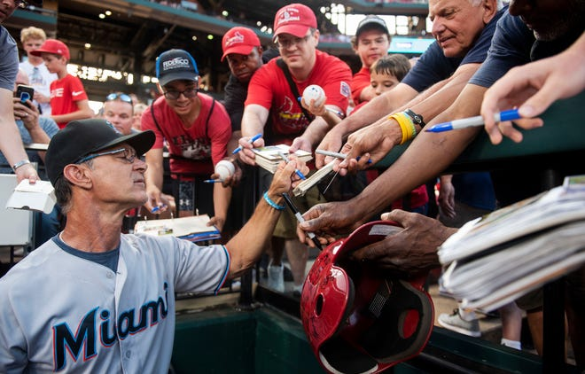 Miami Marlins manager Don Mattingly signs autographs for fans before the start of a baseball game against the St. Louis Cardinals, Tuesday, June 18, 2019, in St. Louis. (AP Photo/L.G. Patterson)