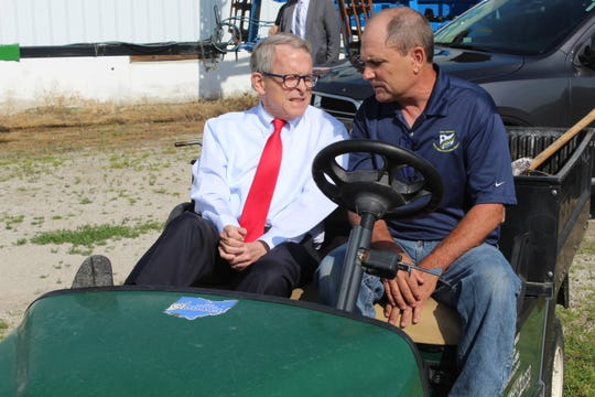Ohio Governor Mike DeWine and Wood County farmer Kris Swartz sit in cart shortly before Swartz showed DeWine part of his farm Wednesday. DeWine paid a visit to Northwest Ohio to speak to farmers and get a sense of the struggles they've faced with heavy rains and saturated fields in recent months.