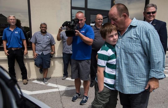 "Cape Coral veteran and single father, Paul Linscott hugs his son Isaiah, 11, after receiving a 2014 Hyundai Elantra on Wednesday morning, June 19, 2019 donated as part of a program entitled ""Recycled Rides."" The presentation was a collaboration between Caliber Collision-Cape Coral, Hertz and the National Auto Body Council."