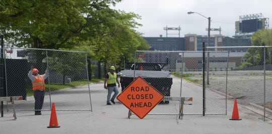 Workers block off Brookwood Drive at Marlee Lane in Ashwaubenon on June 19, 2019, in preparation for construction of townhouses in the Green Bay Packers' Titletown District.
