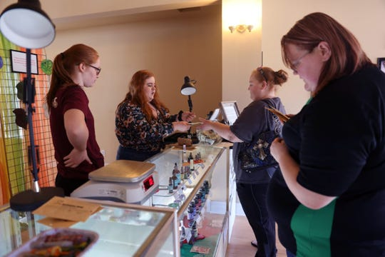 "Tera Jerrett, 34, buys a glass pipe from Isis Murphy-Kehoe, 20, at Kickapoo Kind, a CBD and hemp shop in Viroqua, Wis., on April 19, 2019. Skky Marsden, 27, of Soldiers Grove, at right, looks at products on display as Jerrett, of Readstown, makes her purchase. At left, Serena Murphy-Kehoe, 18, looks on. As she left the shop, Jerrett said, ""I'll be back for sure.""   Isis and Serena are daughters of Kickapoo Kind owners Tim Murphy and Noelle Kehoe."