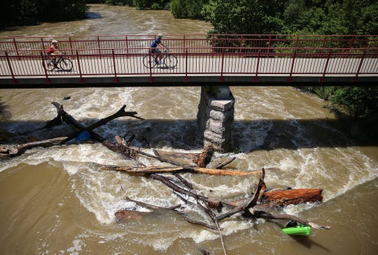 """Cyclists pass overhead as a kayak (bottom right) remains jammed in debris near the Broad Ripple dam of the White River at Westfield Boulevard and 72nd Street, where the river passes below the Monon Trail in Indianapolis, Sunday, July 9, 2017. Two kayakers were in critical condition after being rescued from the """"boil,"""" a rapid churning area of the low-head dam. The force of the water pulled off the life vests that both kayakers had been wearing."""