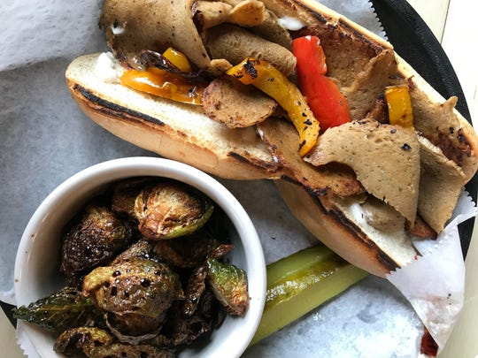 Seitan made in-house joins charred bell peppers and tofu mayonnaise in a submarine sandwich, with roasted Brussels sprouts on the side at 10th Street Diner. The all-vegan restaurant that opened May 11, 2019, at 3301 E. 10th St., Indianapolis.