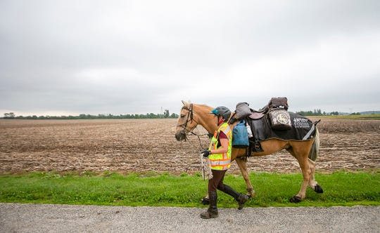 Meredith Cherry walks on the road before climbing on to ride from Oakville to New Castle on Monday, June 10.