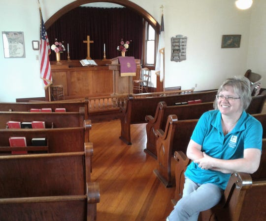 Managing Director Nancy Roth relaxes in a pew at the South Sharon United Methodist Church building located at Kalona Historical Village