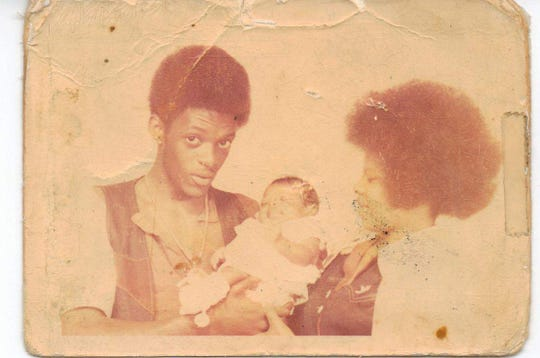 Darryl Butler holds his oldest daughter, LaShawn Butler, as he stands next to her mother.