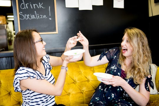 "Knox News reporters Isabel Lohman and Erica Breunlin sample the ""Movie Theatre"" flavor ice cream at It's All So Yummy Cafe, 120 S. Peters Road, in Knoxville on June 18, 2019."