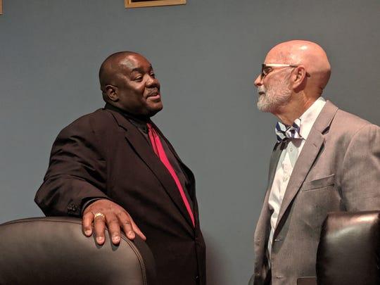 Councilman Kenneth Boudreaux (left) speaks with Councilman Bruce Conque (left)