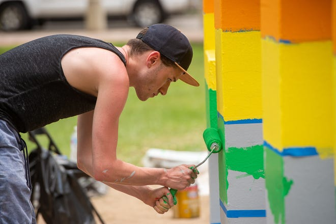 Volunteers from PFLAG Lafayette, an LGBTQ advocacy group,  painting the Lafayette sign in Parc San Souci as part of the Pride Month activities in Lafayette this June. Wednesday, June 19, 2019.