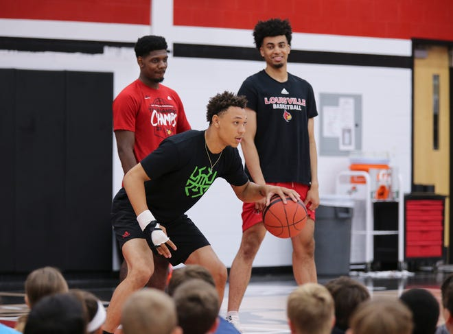 Louisville freshman Josh Nickelberry demonstrates how to dribble while keeping his eyes forward at the Chris Mack Basketball Camp on U of L's campus.  Nickelberry's right hand is bandaged due to an injury.  Teammates Darius Perry and Jordan Nwora, right, looked on. June 19, 2019