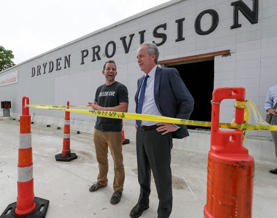 DO/LOVE/LIVE co-founder Dave Childress and Mayor Greg Fischer look out on Butchertown from a roof of the building that will soon house the new brewery.
