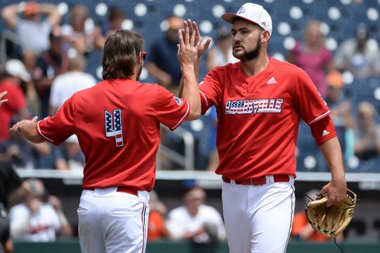 Louisville Cardinals pitcher Michael Kirian (33) greets pitcher Adam Elliott (4) after the win against the Auburn Tigers in the 2019 College World Series at TD Ameritrade Park in Omaha, Nebraska, on Wednesday, June 19, 2019.