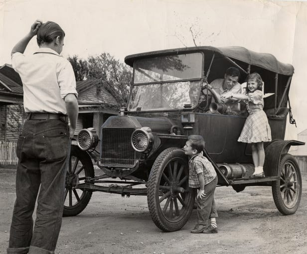 Amazed was the auto-licensing clerk who issued a license for this 1914 Ford, in storage since 1928. Owned by Everett Shannon, it is the object of neighborhood interest. The driver is John H. Kundert, his daughter, Judy, and his son Charles, 5, are fascinated observers, as is Virge Coyler, in the foreground.