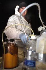 Frank Brian prepares and loads out suspected hazardous chemicals after State Police busted a suspected clandestine methamphetamine lab in a home in Onondaga Township in February 2003. Frank Brian works for an environmental cleanup company that didn't want their name used.