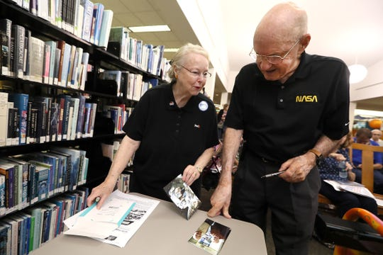 Bill Weppner, a former NASA flight controller who worked on the space program's Apollo missions, chats with Rose Ann Bradley as he signs a few photos before giving a talk about his experiences at the Germantown library Tuesday, June 18, 2019.