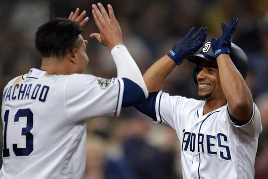 Padres catcher Francisco Mejia (right) is congratulated by third baseman Manny Machado (13) after hitting a two run home run off Brandon Woodruff earlier this year.
