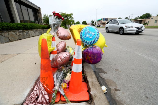 Mourners have contributed to a curbside memorial at North 60th Street and West Capitol Drive for Milwaukee police officer Kou Her, who was killed by drunk driver on his way home from work.