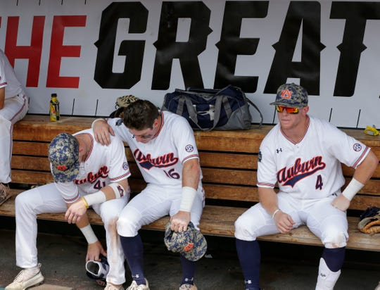 Auburn's Steven Williams (41), Kason Howell (16) and Rankin Woley (4) sit in the dugout following their 5-3 loss to Louisville in a College World Series elimination baseball game in Omaha, Neb., Wednesday, June 19, 2019.