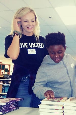 South View Elementary Student James Jackson picks out 12 books with the help of United Way volunteer and Navient employee Heather Crabtree.