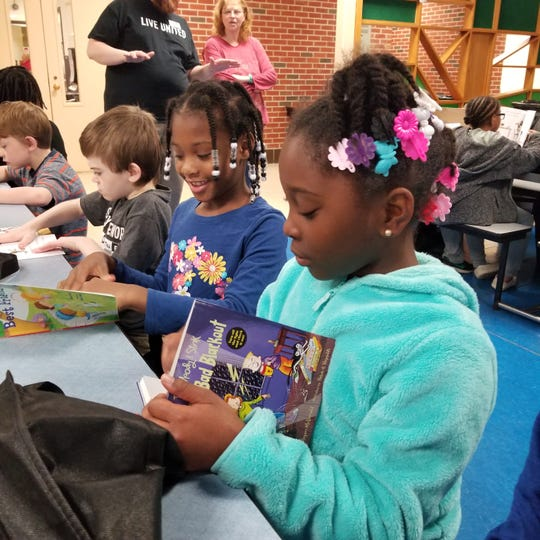 South View Elementary School students Damiyah Watkins, Tionna Canady and Jacob Johnson could not wait to begin reading their new books from the United Way's Summer Book Give Away.