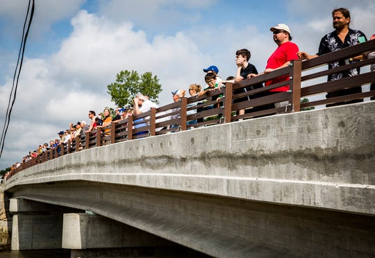 A crowd gathered to watch as a construction crew positioned a restored, historic bridge, once located near Albany, across the White River at the east entrance to Muncie on E. Jackson Street Wednesday morning.  Once a path is laid across the newly placed bridge, it will act as a connecting point between the Cardinal Greenway and the White River Greenway which run alongside opposite banks of the river.