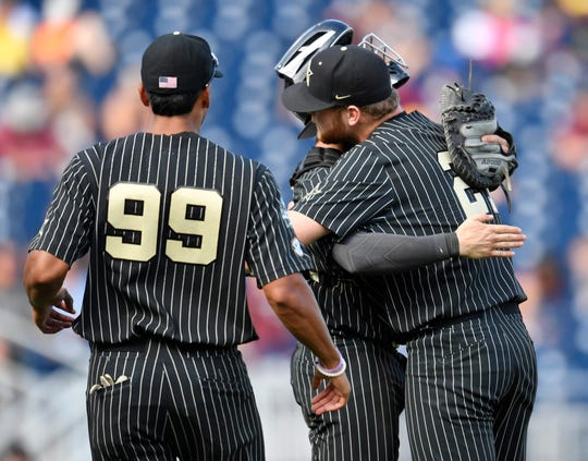 Vanderbilt pitcher Tyler Brown (21) is hugged by Vanderbilt catcher Philip Clarke (5) after getting the save in the team's 6-3 win over Mississippi State in the 2019 NCAA Men's College World Series at TD Ameritrade Park Wednesday, June 19, 2019, in Omaha, Neb.