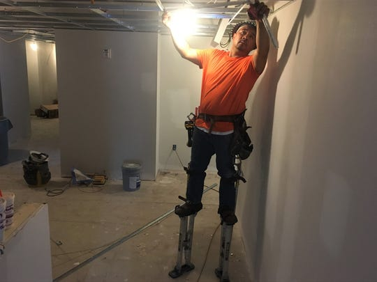 A subcontractor installs hardware for ceiling panels in the future building for Recovery Unplugged, the first inpatient substance abuse treatment center in Brentwood.