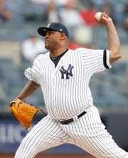 New York Yankees starting pitcher CC Sabathia (52) pitches against the Tampa Bay Rays in the first inning  at Yankee Stadium.