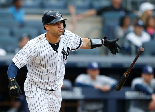 New York Yankees catcher Gary Sanchez (24) tosses his bat after hitting a home run in the first inning against the Tampa Bay Rays at Yankee Stadium.