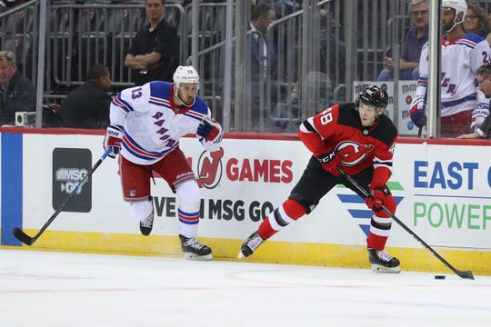Sep 17, 2018; Newark, NJ, USA; New Jersey Devils defenseman Ty Smith (48) plays the puck while being defended by New York Rangers center Kevin Hayes (13) during the first period at Prudential Center.