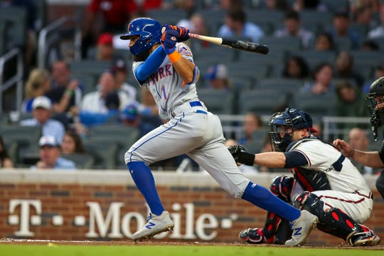 Jun 18, 2019; Atlanta, GA, USA; New York Mets shortstop Amed Rosario (1) hits a RBI single against the Atlanta Braves in the third inning at SunTrust Park. Mandatory Credit: Brett Davis-USA TODAY Sports