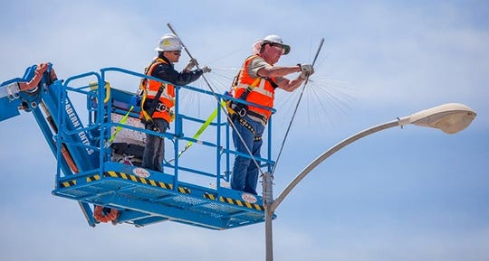 Workers install dandelion-shaped arrays atop light poles as part of upgrades to Waste Isolation Pilot Plant's lightning protection system. The arrays fill gaps in the existing system.
