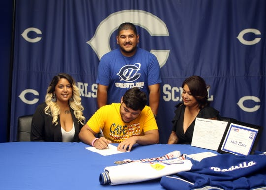 Fabian Padilla signs his letter of intent to attend Iowa Western CC on a wrestling scholarship on Tuesday at Carlsbad High. Padilla ended his high school career with a state title and became the first Carlsbad wrestler in two decades to achieve All-American status as a wrestler.