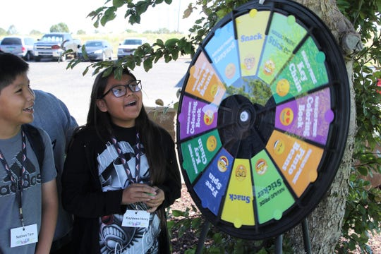Kaylanna Henry of Kirtland, right, spins the emoji wheel to find out what kind of free prize she will win while touring the Navajo Agricultural Products Industry just outside Farmington on Wednesday.