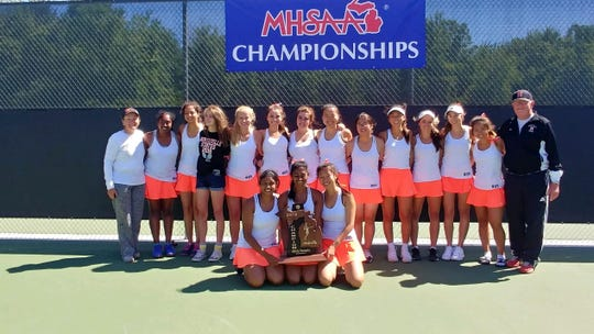 The Northville girls tennis team poses after winning the 2018 state championship. Coaches Linda and Dan Jones stand at either side.