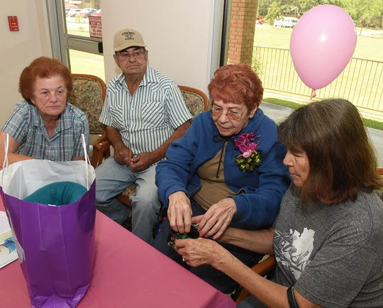 Nelda Stelly, second from right, opens her gifts as she recently celebrated her birthday at Prompt Succor Nursing Facility. From left are Judy Credeur, Harold Credeur and Annie Miller.