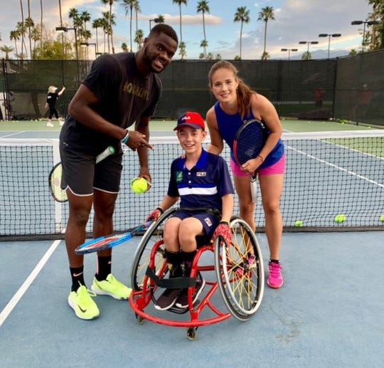 Charlie Cooper, an 11-year-old wheelchair tennis player from La Quinta, poses with pro tennis players Frances Tiafoe (left) and Genie Bouchard.