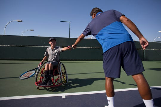 Charlie Cooper is a youth wheelchair tennis player who is Ranked No. 3 in the U.S. He is photographed at Indian Wells Tennis Garden as he high-fives his coach Jai Nettimi.