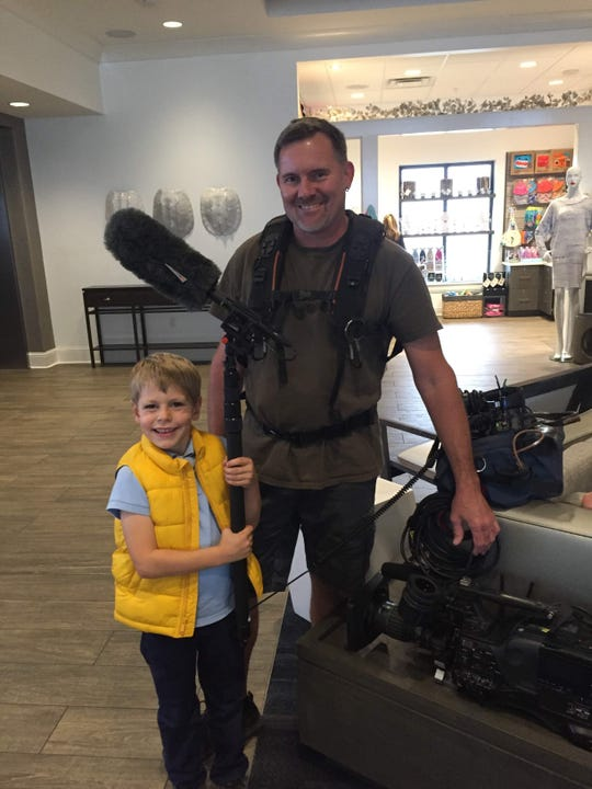"Henry Newcamp, 7, learns about sound and camera equipment with a member of the production team of ""House Hunters"" while filming an episode of the show in November 2018."