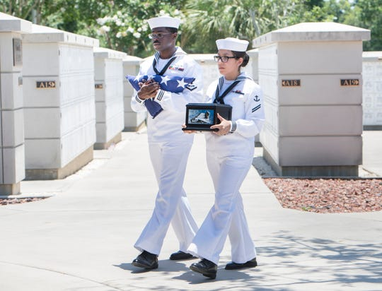 Petty Officers James Johnson, left, and Janet Nunez carry the American flag and veteran's remains during a funeral at Barrancas National Cemetery at NAS Pensacola on Friday, June 14, 2019.
