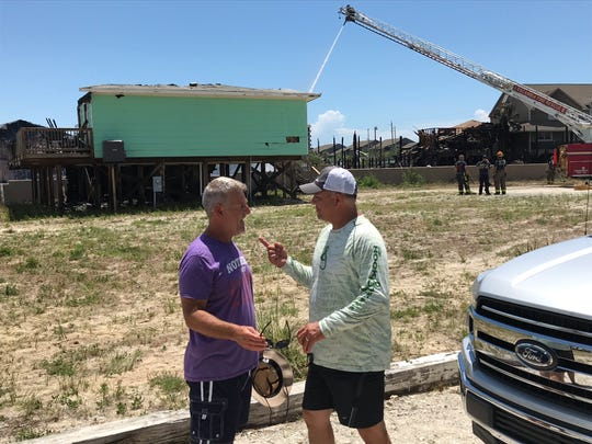 Mark Daigle, left, and Dennis Marceaux talk Wednesday about the fire that ripped through Perdido Key and destroyed 26 condo units and one home.